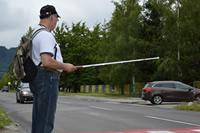 Muž s bielou palicou na priechode pre chodcov