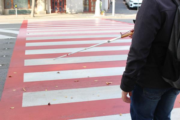 Nevidiaci vchádza s bielou palicou na priechod pre chodcov a zodvihnutím signalizuje, že chce prejsť. Autor: Tomáš Bako