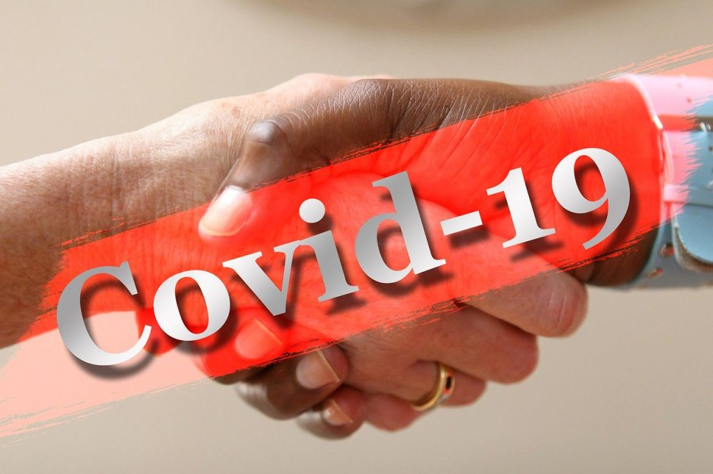 Dve podávajúce sa ruky prečiarknuté červeným nápisom Covid-19