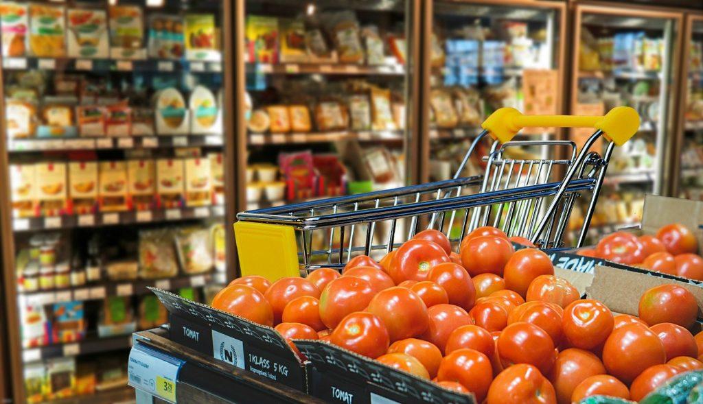 Prázdny nákupný košík v priestoroch obchodu, stojaci pri paradajkách, v pozadí sú chladničky s tovarom.