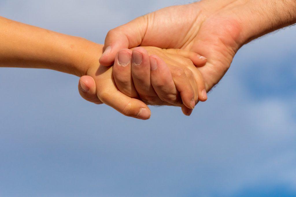 Na obrázku sú dve ruky, ktoré sa navzájom držia.
