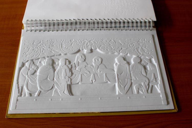 Stránka knihy s motívom Poslednej večere Majstra Pavla z Levoče v reliéfnom vyobrazení.