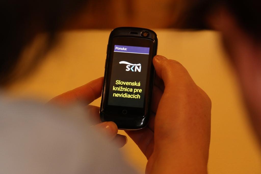 Ruky držiace telefón, ktorý má na displeji logo knižnice a text: Slovenská knižnica pre nevidiacich.