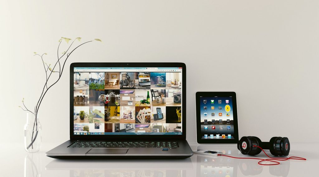 Ilustračný obrázok k téme: Na stole je PC so slúchadlami a pri nich tablet.