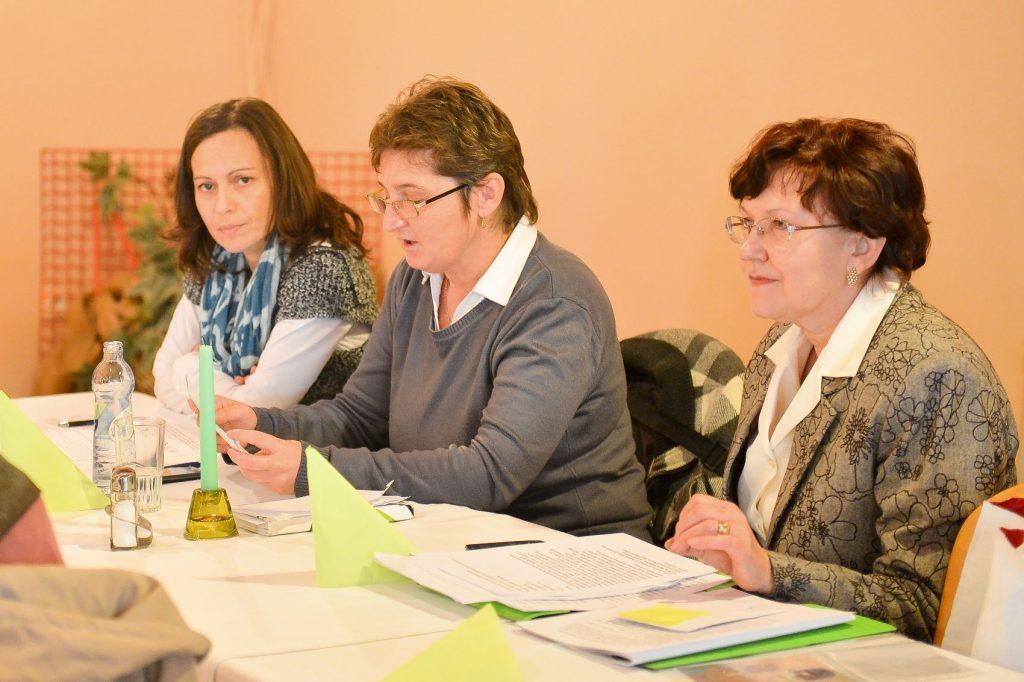 Za stolom sú počas členskej schôdze tri ženy, jednou z nich je p. M. Zubáková.