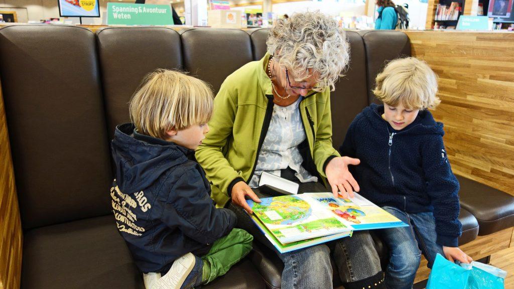 Na fotografii sedí stará mama s knihou na kolenách, pri nej je z každej strany malý chlapec. Spoločne hľadia do atlasu.