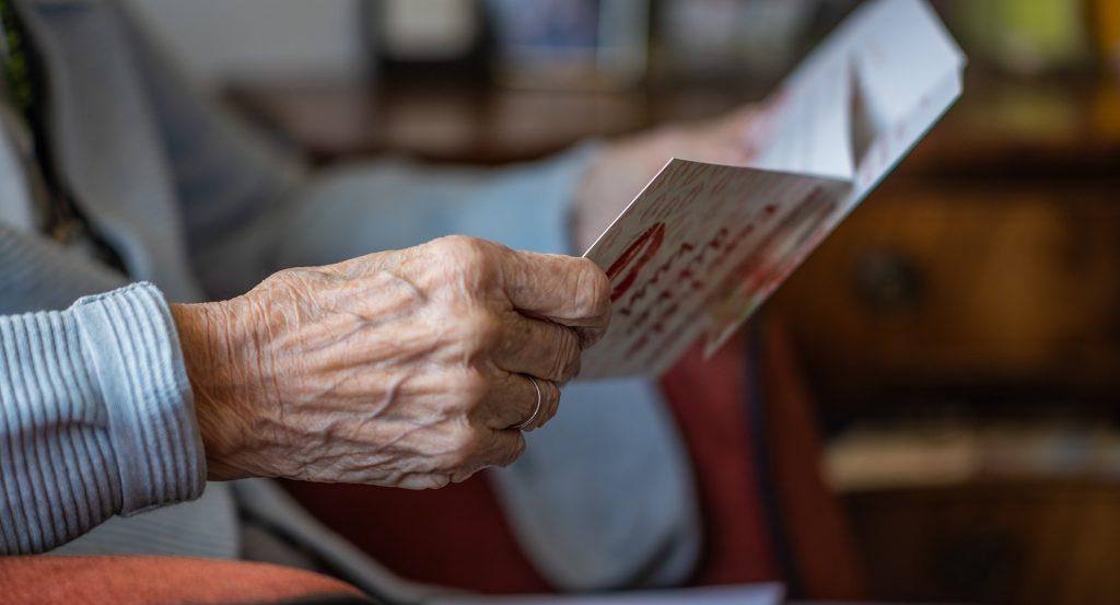 Detail rúk seniorky, ktorá má v rukách pozdrav alebo kartičku.