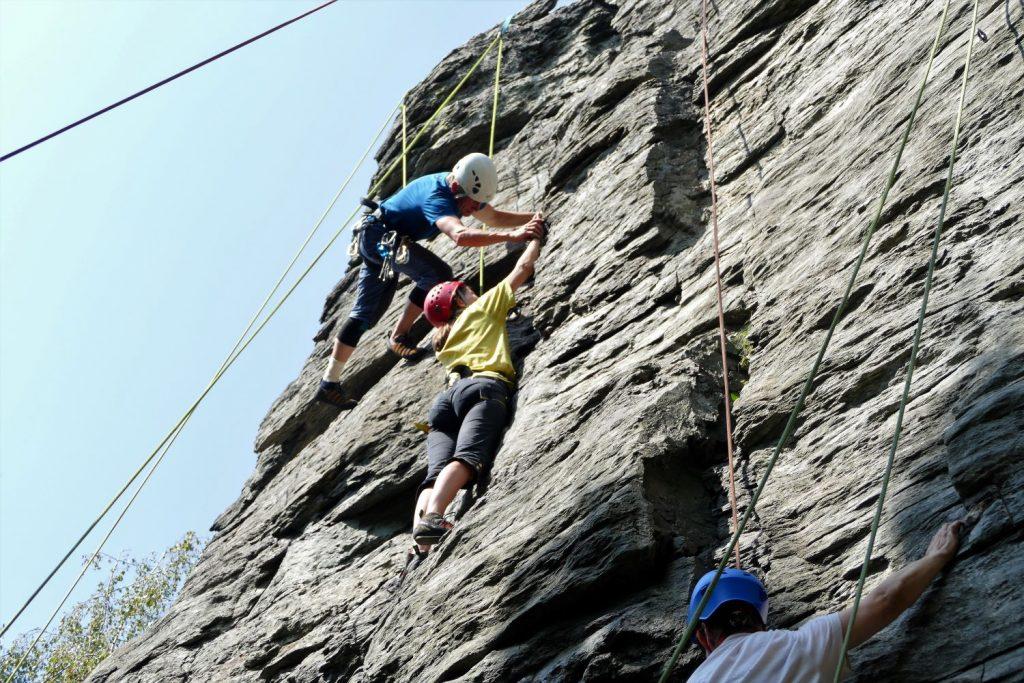 Na skale visia laná a za ne sú zachytní lezci. Muž pomáha žene s uchýtom ruky.