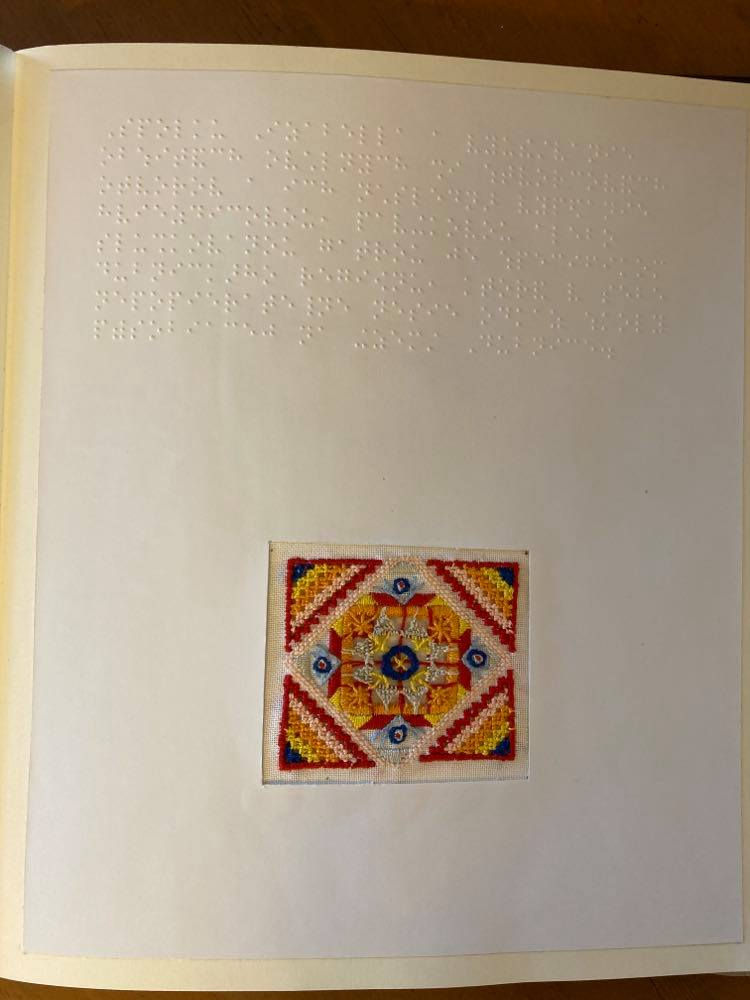 Stránka z knihy, hore popisok v Braillovom písme a nižšie štvorec zdobený drobnou pestrofarebnou výšivkou.