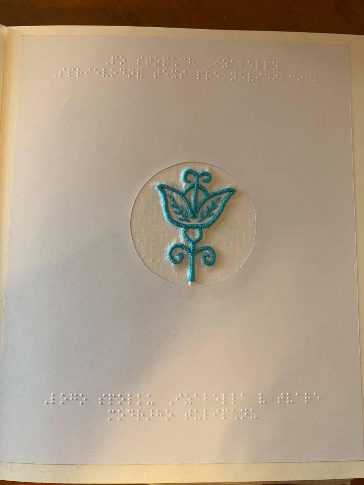 Stránka knihy, hore a dolu popisok v Braillovom písme a uprostred výšivka - modrý tulipán.
