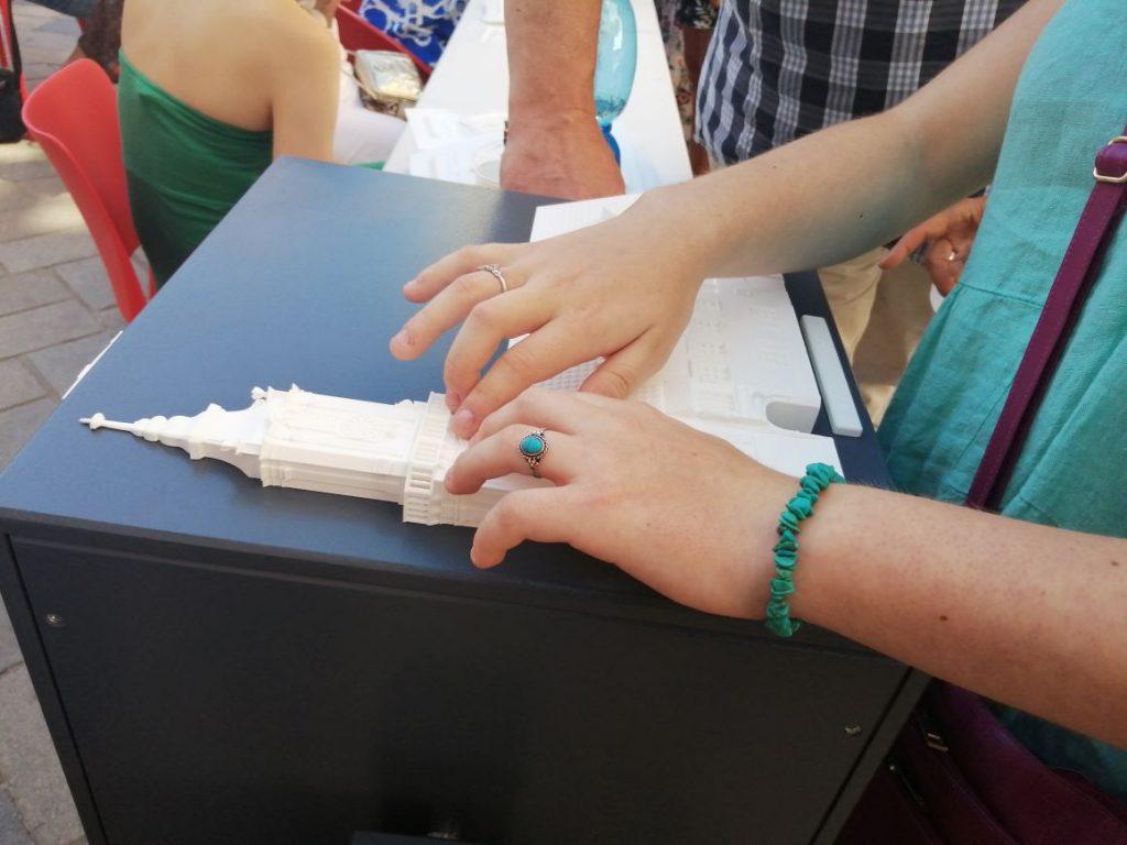 Na obrázku sú ruky návštevníčky skúmajúce vežu kostola na jednej z kociek.